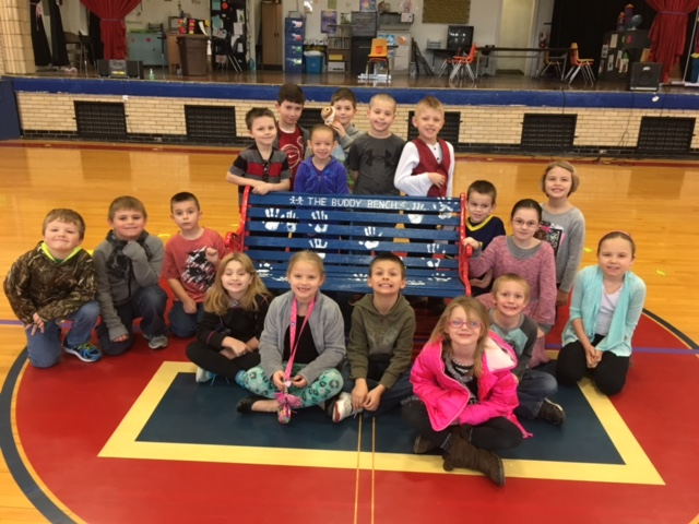 Elementary students posing with the buddy bench they created