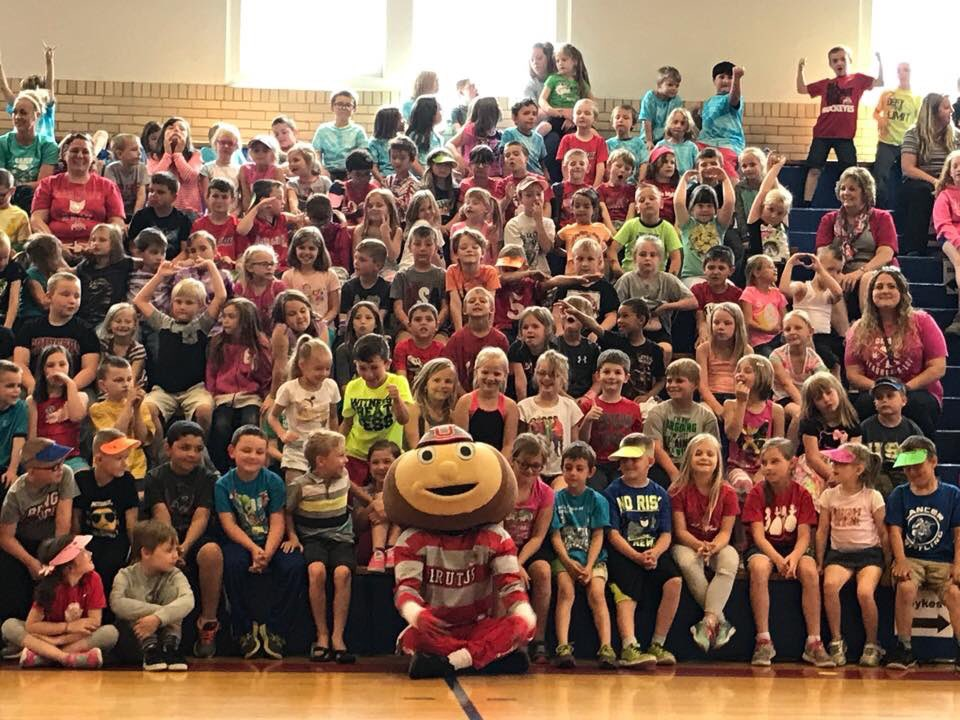 large group of elementary students posing on the bleachers with Brutus Buckeye