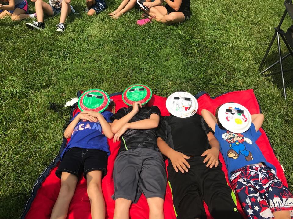 students laying on the ground with paper plates made into protective eye wear to watch the solar ecl