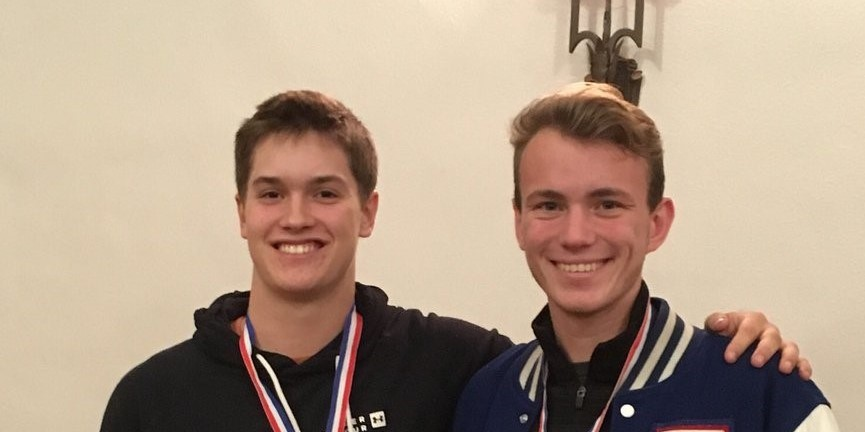 2 students posing with medals