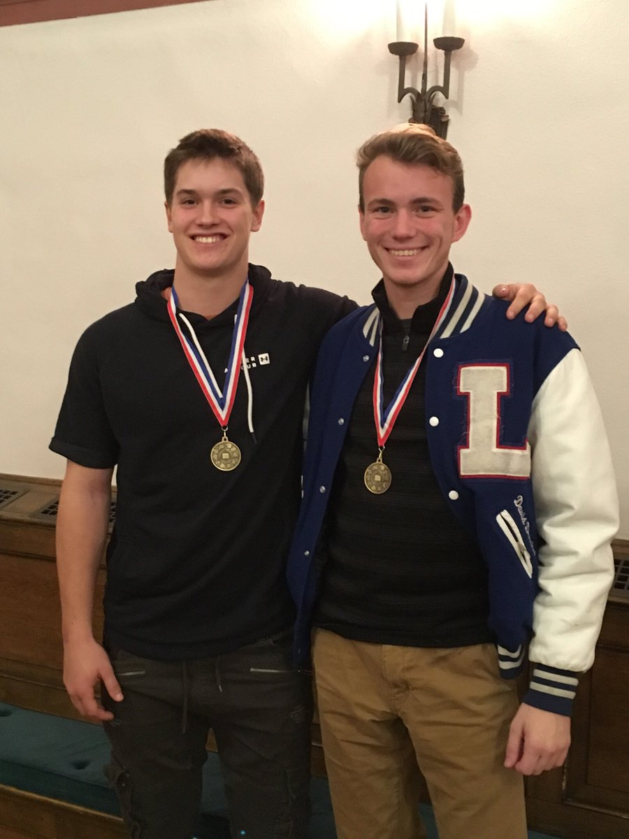 2 student athletes wearing medals