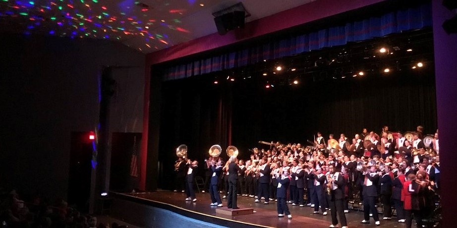 marching band performing on stage in auditorium with disco lights
