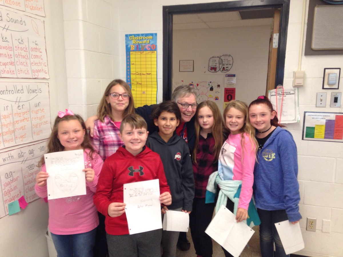 group of students posing with school principal Mrs. Field showing the thank you notes they wrote