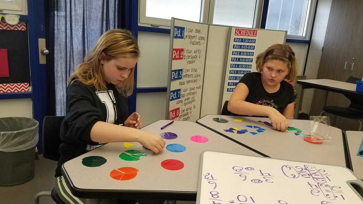 2 female students using charts to learn fractions