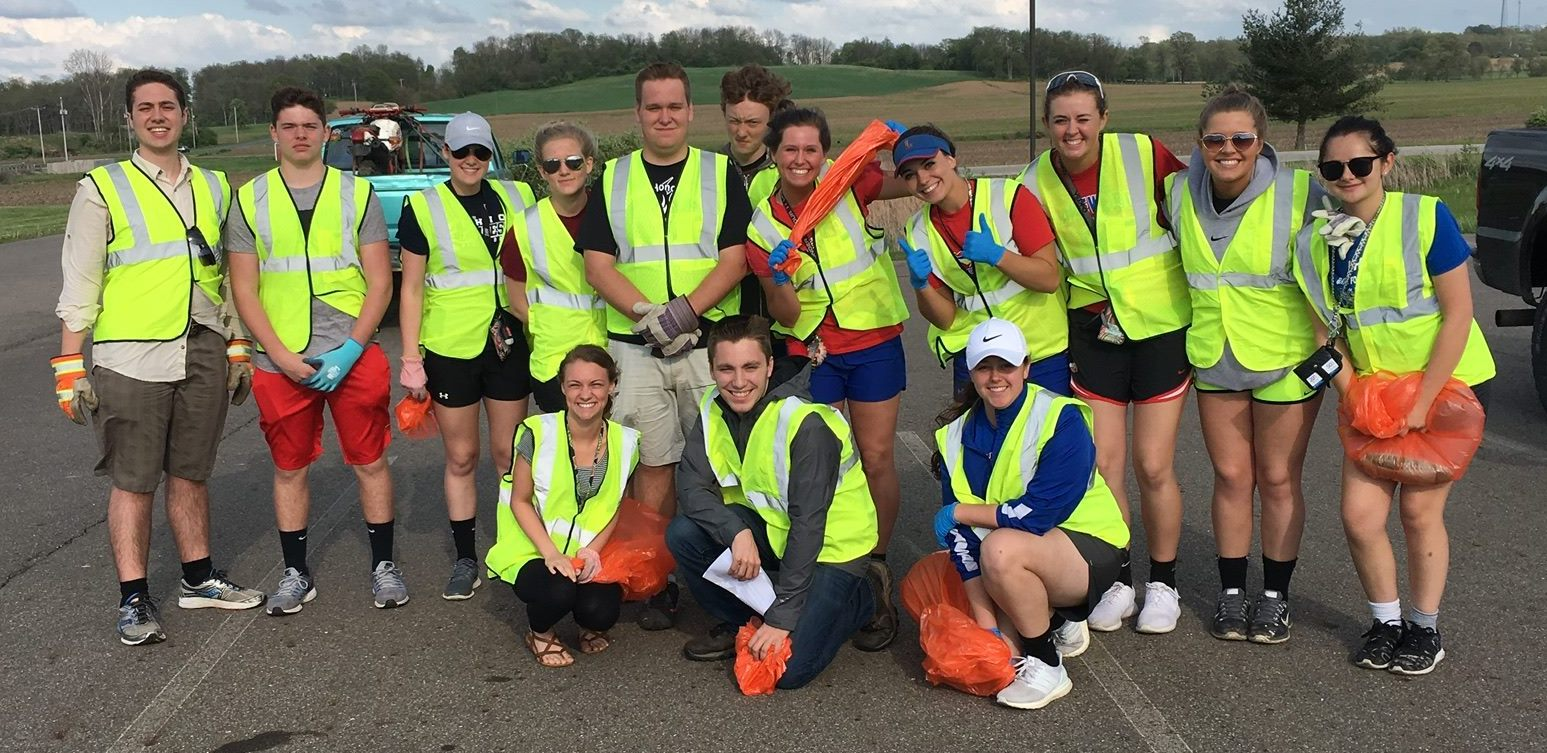 Students dressed in neon vests preparing to pick up litter on Route 40