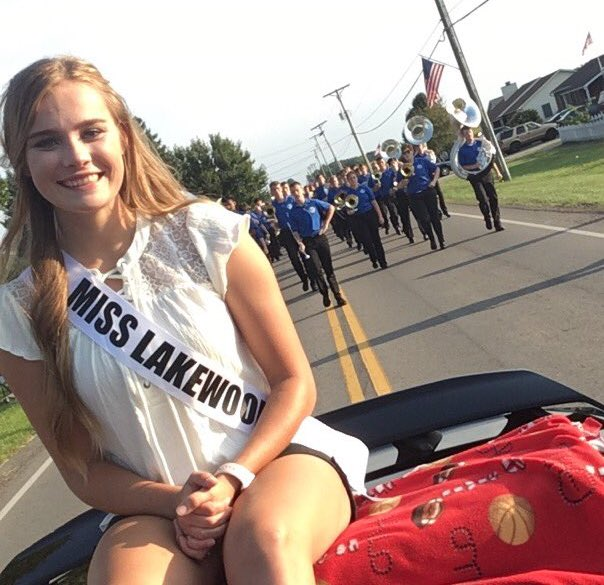 Lakewood's representative riding on the back of a car in the Sweet Corn Festival parade with the Lak