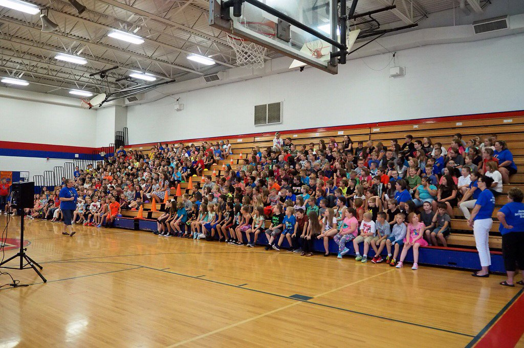 Students sitting in bleachers for an assembly about school rules.