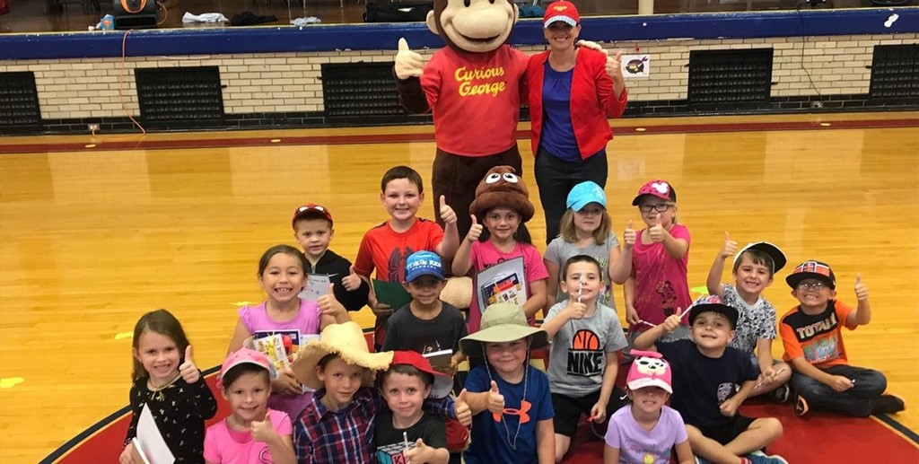 Students posing with Curious George for reading program recognition