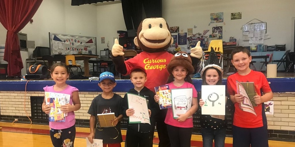 Students posing with curious george for design challenge recognition