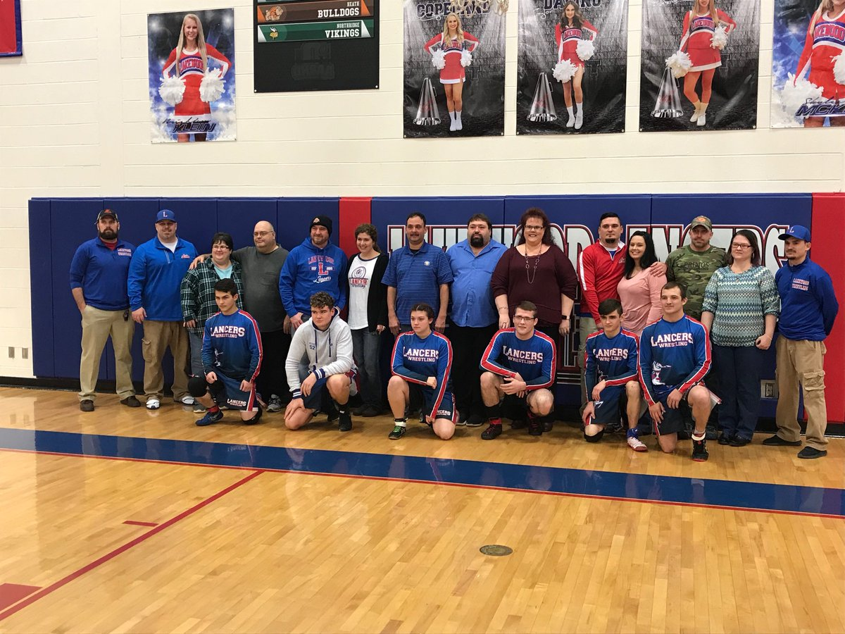 senior wrestlers and parents pose for picture