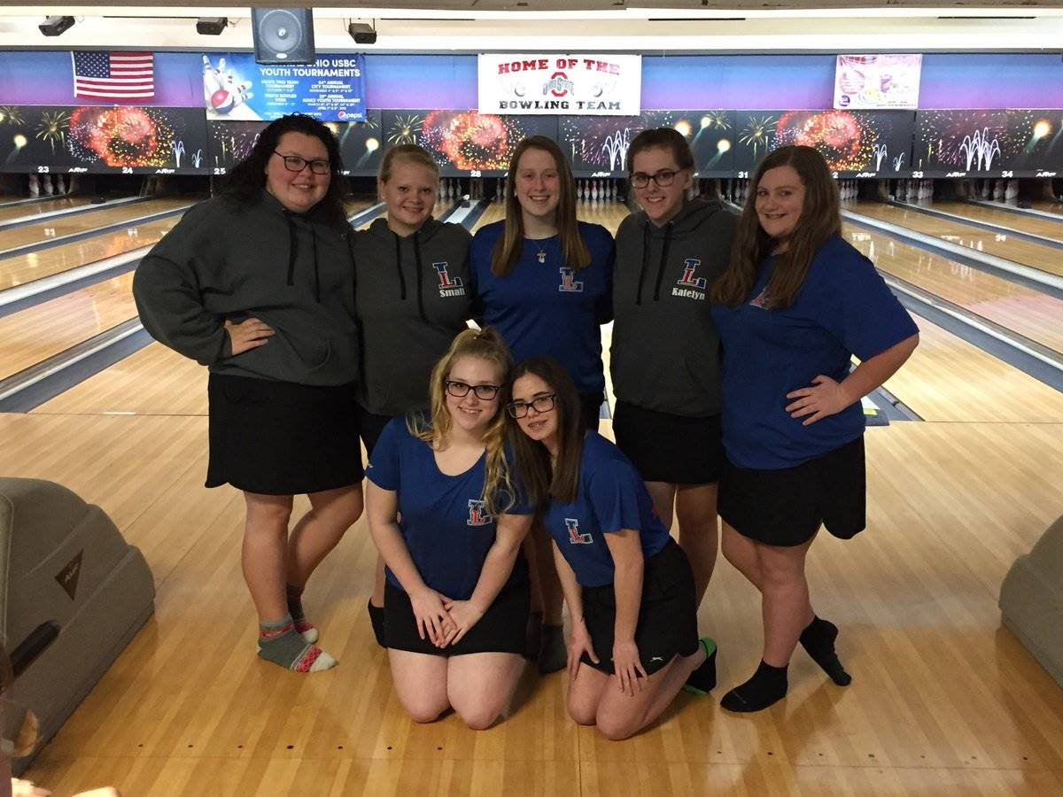 Girls bowling team posing for a picture at the bowling alley
