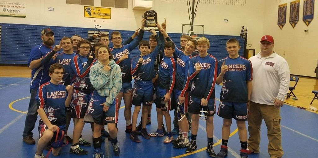 group of wrestlers posing with trophy