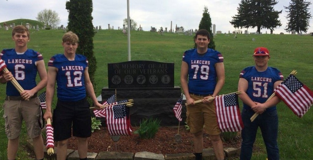 Football players placing flags for Memorial Day