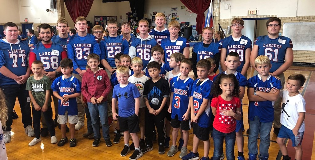 LHS football players pose with Hebron students