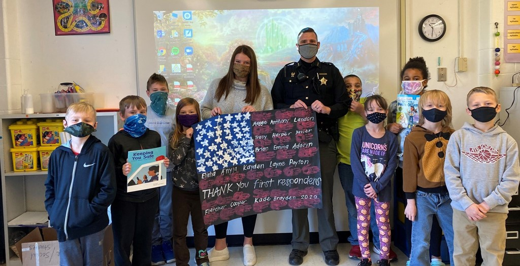 students posing with Resource Officer to share a project they did to honor first responders