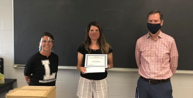 Mrs. Londberg receiving award from Mrs. Fry and Dr. Gleichauf